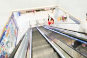 image of escalator  - Unfocused view of shopping mall from escalator  - JPG