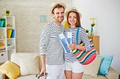 stock photo of amor  - Amorous and happy couple with airtickets looking at camera - JPG