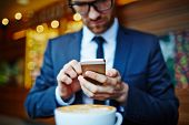 stock photo of sms  - Young businessman writing sms in cafe - JPG