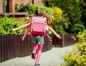 foto of little school girl  - little girl with a backpack run  to school - JPG