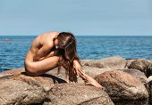 pic of nude women  - BW image of beautiful young sexy nude woman siting on stones by the sea - JPG