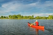 foto of collins  - male paddler paddling a red canoe on a local lake in Fort Collins - JPG