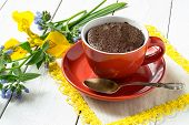 picture of chocolate spoon  - Chocolate cake and quick cooking in a red cup a spoon and flowers on white wooden table - JPG