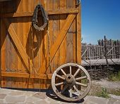 stock photo of wagon wheel  - old wooden wagon wheel near the open gate - JPG