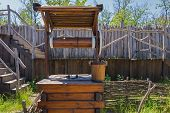 stock photo of water well  - well with a wooden roof and a bucket of water - JPG