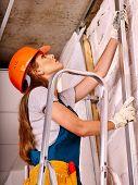 stock photo of millwright  - Happy woman in builder uniform and helmet  indoor - JPG