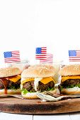 foto of beef-burger  - American mini beef burgers with cheese and USA flagsselective focus and blank space - JPG