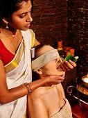 stock photo of ayurveda  - Woman having fresh leaf nose ayurveda spa treatment - JPG