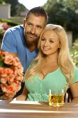 stock photo of cleavage  - Portrait of romantic young couple sitting at summer garden - JPG