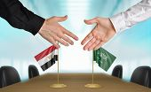 stock photo of saudi arabia  - Two diplomats from Egypt and Saudi Arabia extending their hands for a handshake on an agreement between the countries - JPG