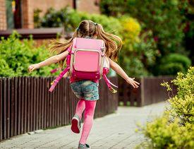stock photo of schoolgirl  - little girl with a backpack run  to school - JPG