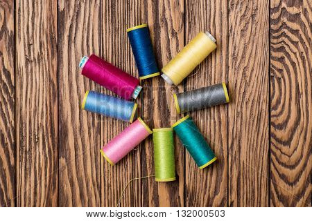 Spools of threads on the wooden background.