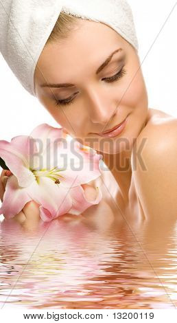 Beautiful young woman with pink lily reflected in rendered water
