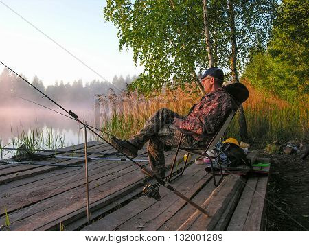 Fisherman meets sunrise on the bank of forest lake