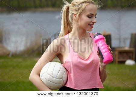 summer vacation, sport and people concept - young woman with ball playing volleyball