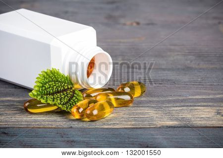 Alternative medicine pills in white plastic container with green leaves