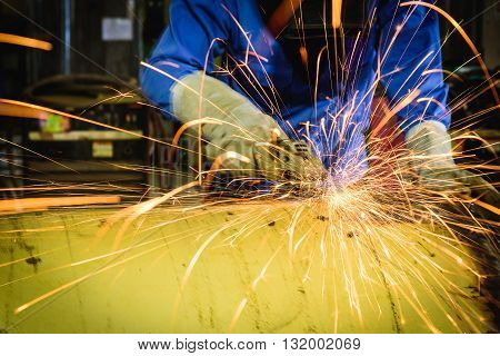 Grinding machine in action with bright sparks in construction factory.
