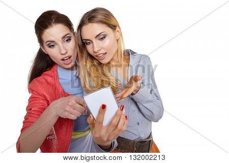 Two happy women friends sharing social media in a smart phone
