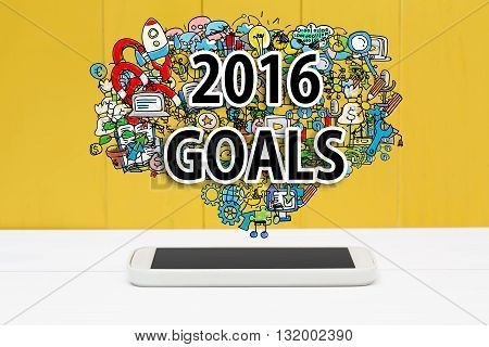 2016 Goals concept with smartphone on yellow wooden background