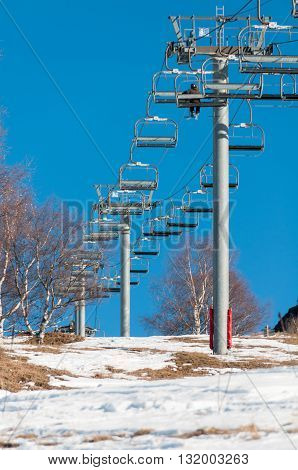 A man takes a ride in a ski lift up the hill on a day in spring with few snow and blue sky