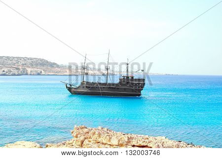 pirate sailing ship on the background of bright blue sea and sky