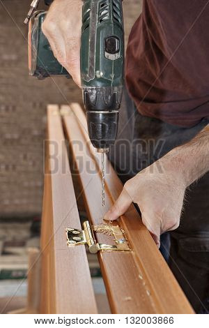 Wireless electric drill in the hands of a carpenter drilling holes for fastening brass door hinges in wooden interior door close-up.