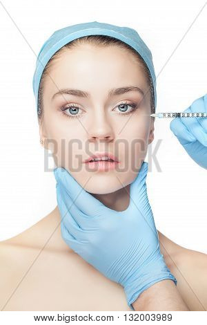 Attractive woman at plastic surgery with syringe in her face on white background
