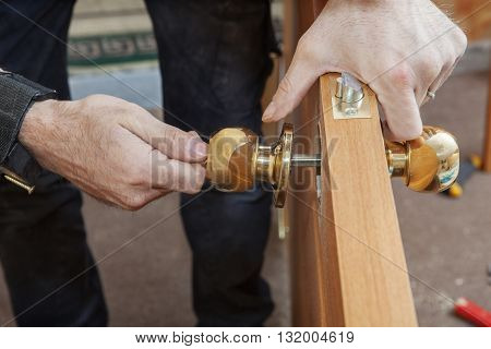 Carpenter Change door Installing new door knob with lock close-up human hend hold door handle.