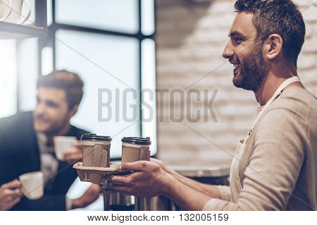 Your coffee to go! Side view of barista passing coffee cups to his customer with smile while standing at bar counter