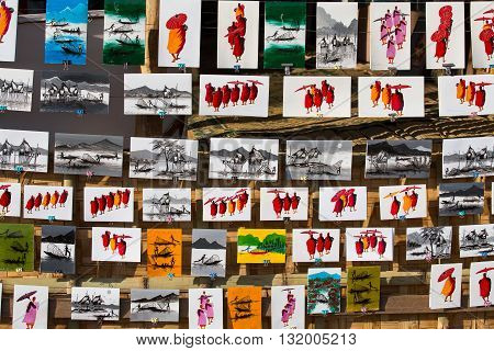 INLE LAKE MYANMAR - JANUARY 12 2016 : Paintings of monks and Inle lake are sold as souvenirs in market.