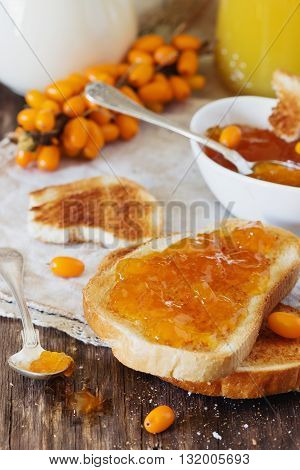 Toast with homemade sea buckthorn jam and ripe sea buckthorn berries on a table. Healthy breakfast. Health and diet food. Selective focus