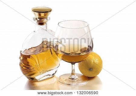 Bottle and a snifter of brandy with an orange on a white background