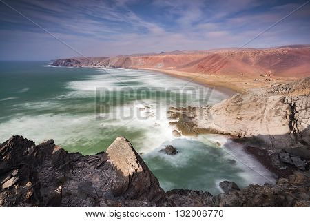 Panoramic colorful coastline with a view over a small bay with a few fishing lodges at the Atlantic Ocean near Sidi Ifni in Morooco, Africa