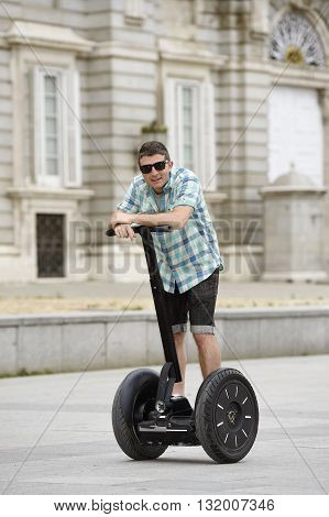 young happy tourist man riding city tour segway driving happy and excited visiting Madrid palace in Spain having fun in urban transport concept