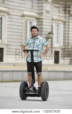 young happy tourist man wearing safety helmet headgear riding city tour segway driving happy and excited visiting Madrid palace in Spain having fun in urban transport concept