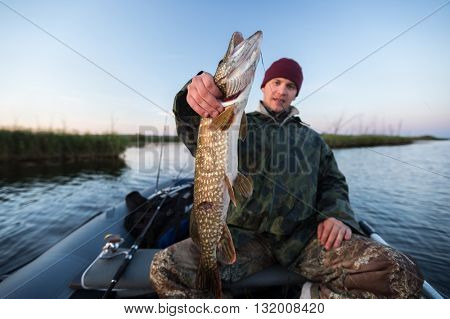 Young fisherman holding pike and sitting in the boat on the lake