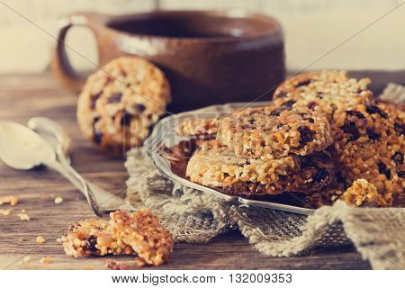 Homemade cookies from sesame seeds raisins and caramel on the old wooden background. Toned image. Selective focus