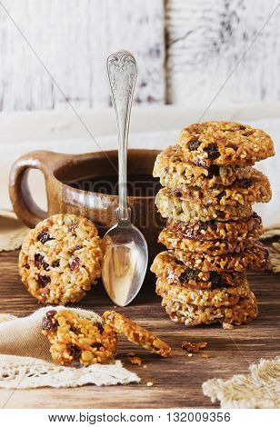 Homemade cookies from sesame seeds raisins and caramel on the old wooden background. Selective focus
