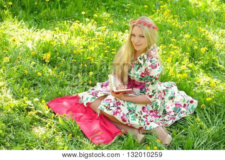 Beautiful woman sitting on the grass and wrote in his diary