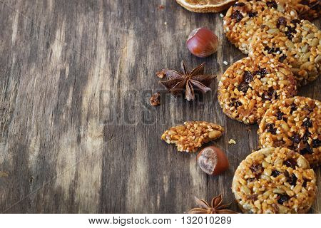 Homemade cookies sesame raisins and caramel on the old wooden background. Copy space for you text