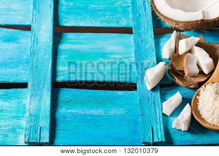 Half coconut with wedges of coconut and shreds on bright blue wooden background