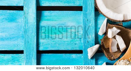 Half coconut with wedges of coconut and shreds on bright blue wooden background. Banner size image. Copy space