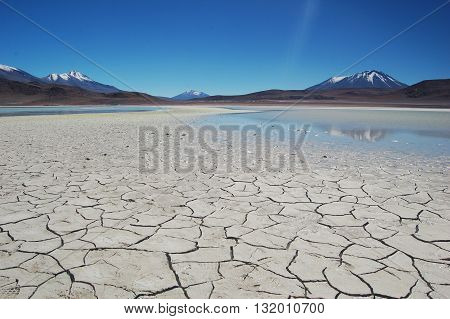 Dry Lake Surrounded By Mountains and Blue Sky