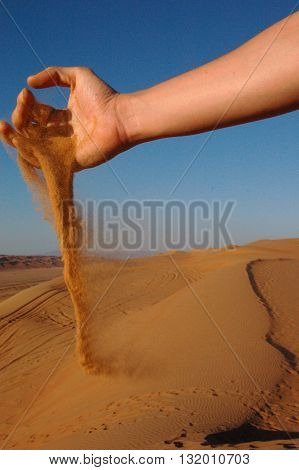 Sand Grains Slipping and Falling Through Hand