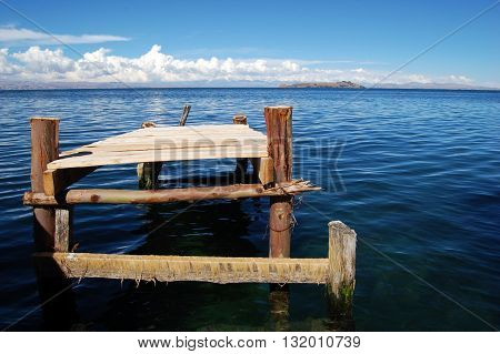 Old small wood pier / jetty in blue water with blue sky