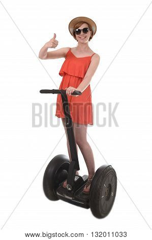 young attractive tourist woman in chic summer dress smiling happy riding electrical segway giving thumb up having fun driving isolated on white background in ecological transport concept