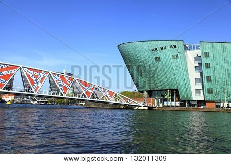 AMSTERDAM, NETHERLANDS - MAY 6, 2016: View of bridge and Science Center NEMO designed by Renzo Piano (1997) - largest childrens science educational museum and center of tourism in Amsterdam, Netherlands.