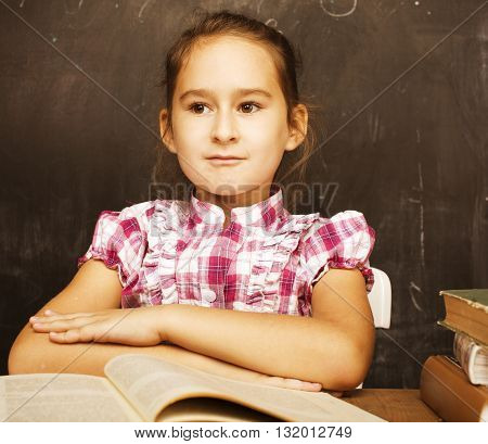 little girl sitting in classroom at blackboard with book, good pupil, lifestyle people concept