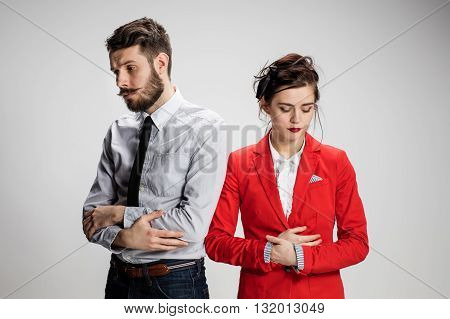 The funny sad business man and woman conflicting on a gray background. Business concept of relationship of colleagues