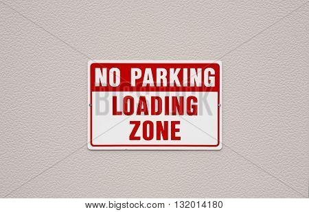 No parking loading zone sign on exterior wall surface.